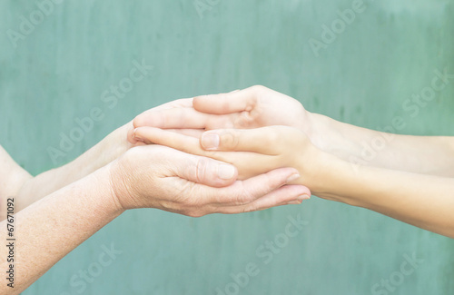 caring hands of a young girl and an old woman