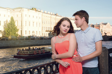 Young man and woman stand on the city embankment