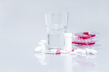 medicines on white with a glass of water