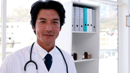 Handsome young doctor smiling at camera