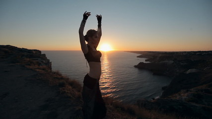 Stunner girl dancing oriental dance at sunset