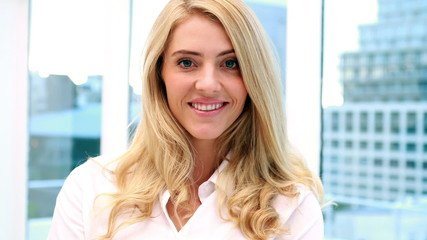Pretty blonde businesswoman smiling at camera