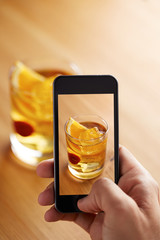 Smartphone taking a picture of cocktail