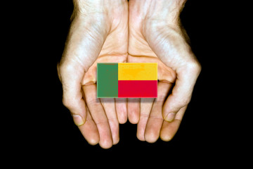 Flag of Benin in hands on black background