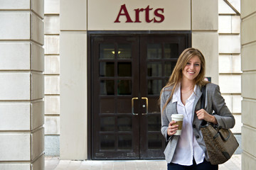 Portrait of attractive female university student outside campus