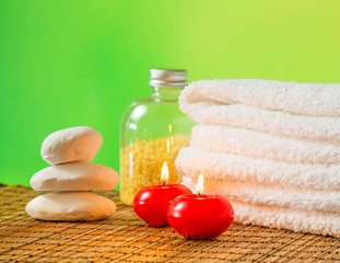 Spa massage with towel stacked,red candles and stone