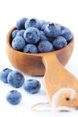 Fresh blueberries in a rustic wooden scoop