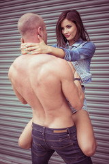 Shirtless man carrying female model