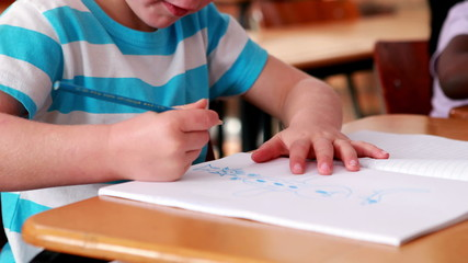 Little boy colouring in the classroom
