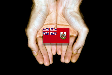 Flag of Bermuda in hands on black background