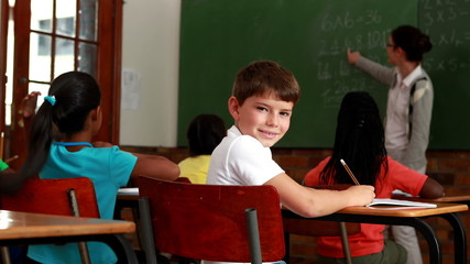 Little boy turning to smile at camera during class