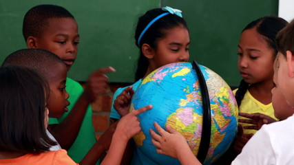 Pupils looking at the globe in classroom