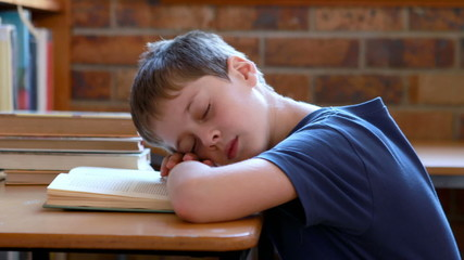 Little boy sleeping on a book in classroom