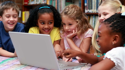 Pupils using the laptop together in the library