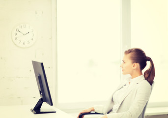 businesswoman looking at wall clock in office
