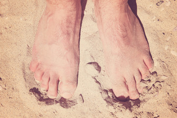 Male bare feet in a warm sand on a sunny beach during vacation