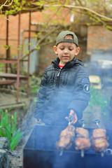 A boy prepares kebabs
