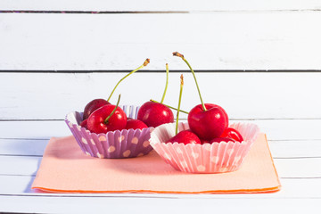 Two cupcake liners filled with cherries.
