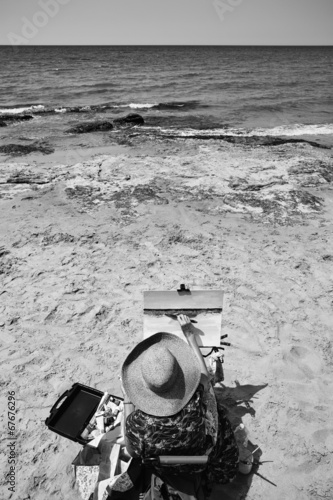Italy, Sicily, Donnalucata, woman painting on the beach
