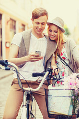couple with smartphone and bicycles in the city