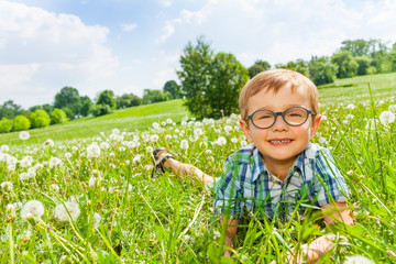 Little boy smiles laying on a grass