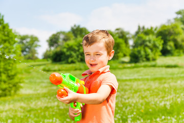 Little boy plays with a water gun