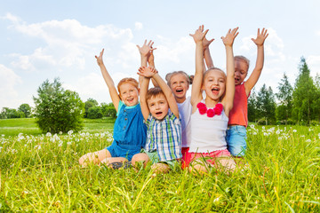 Funny children sitting on a meadow