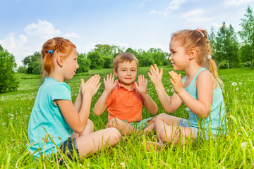 Three kids playing on a grass