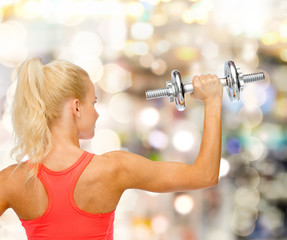 sporty woman with heavy steel dumbbell from back