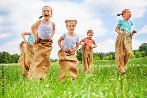 Leinwanddruck Bild Five kids jump in sacks
