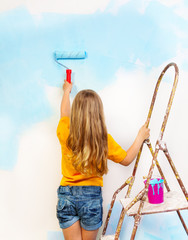 Little girl paints the wall standing on a ladder