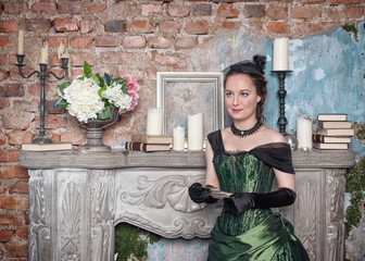 Beautiful woman in medieval dress near fireplace