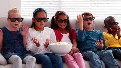 Cute children watching 3d movie on the sofa