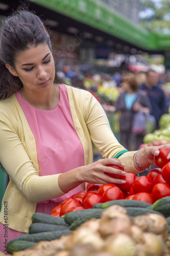 canvas print picture Pretty young woman buying vegetables on the market