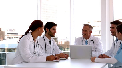 Medical team meeting together with laptop