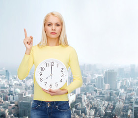 student with wall clock and finger up