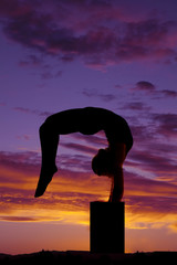silhouette of woman dancing legs behind head off ground