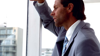 Unhappy businessman looking out window