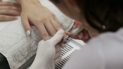 Finger nail treatment, grinding and polishing in beauty salon