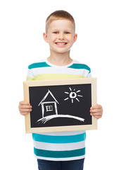 smiling little boy holding chalkboard with home