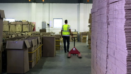 Warehouse worker pulling trolley away form camera