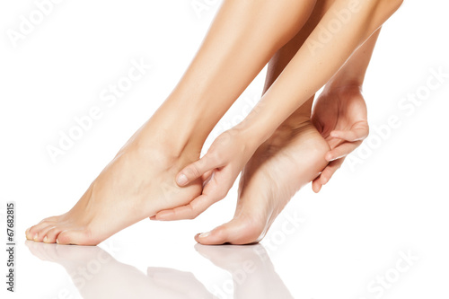 woman tenderly touching her feet - 67682815