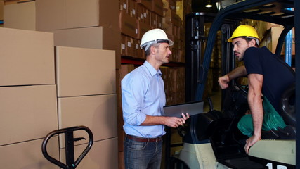 Warehouse manager working with foreman in forklift