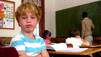 Bored little boy blowing through lips during class