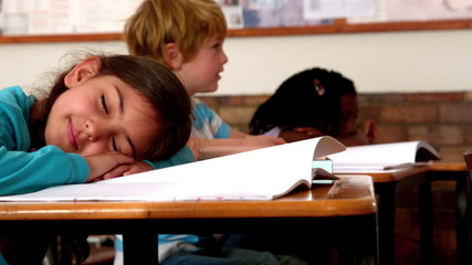 Cute little girl sleeping on desk during class