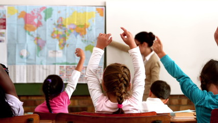 Young pupils raising hands during geography lesson in classroom