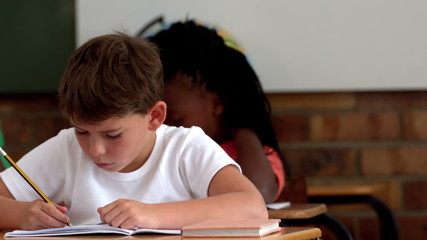 Little boy writing in notepad in classroom