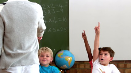 Cute pupils lifting their hands in classroom