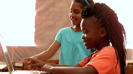 Little girls using laptop in classroom