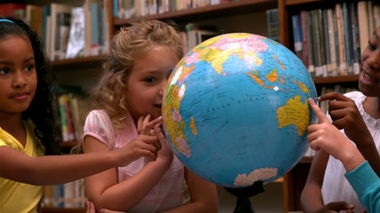 Cute little girls looking at globe in library